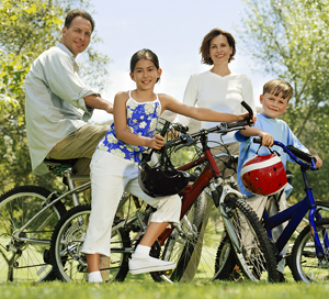 Man, woman, and two children on their bikes in a park