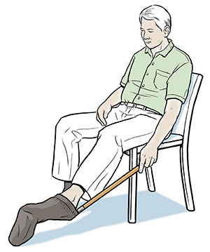 Seated man using long-handled sock donner.