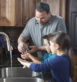 Man helping boy and girl wash hands in sink.