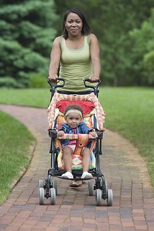 Young mother walking with baby carriage in park.