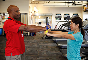Physical therapist showing woman resistance band exercise.