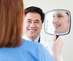 Woman looking in hand mirror with healthcare provider looking on.
