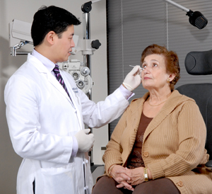 Woman sitting on exam chair. Healthcare provider is examining woman's eye.