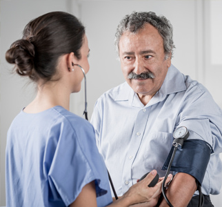 Healthcare provider taking blood pressure of an older man