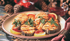 Grilled salmon steaks on a plate with lemon and tomato slices.