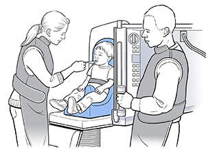 Small boy sitting in child seat on X-ray machine. Health care provider is feeding boy from spoon. Another health care provider is standing nearby.