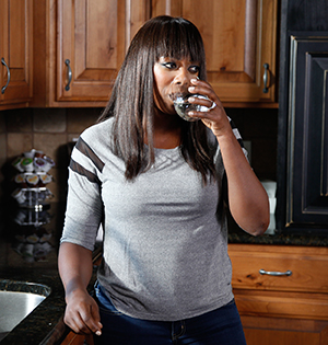 Woman having glass of water at kitchen sink.